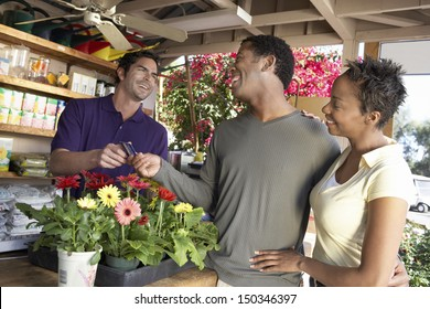 Happy African American couple paying for plants in nursery