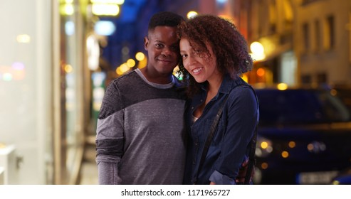 Happy African American couple pose for a portrait in the city at night