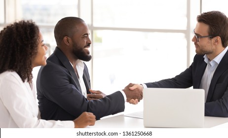 Happy african american couple shake hand of insurer salesman buy insurance services, black family clients customers handshake caucasian realtor broker make sale purchase deal agreement take bank loan