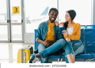 happy african american couple sitting in departure lounge with baggage and air tickets in airport