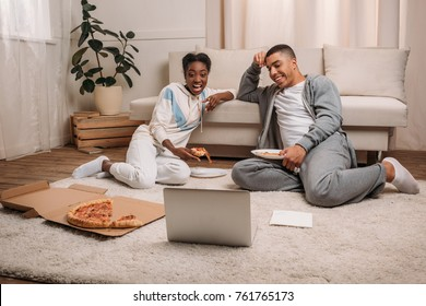 happy african american couple sitting on carpet beside couch, eating pizza and watching something on laptop at home