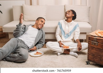happy african american couple sitting beside sofa and eating pizza at home