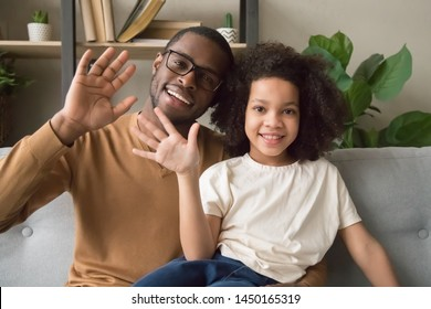 Happy african American dad and daughter sit on couch wave talking on webcam having skype conversation, smiling black father and girl child blogger say hello to viewers record youtube vlog or blog