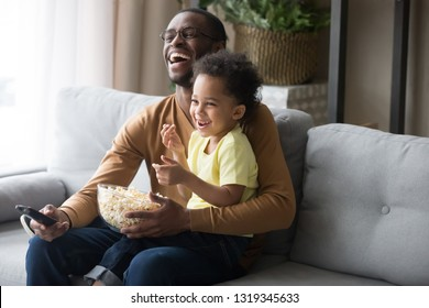 Happy african american dad and kid son laughing holding popcorn remote control watching funny comedy movie tv show sitting on sofa, black father having fun with child boy viewing television at home