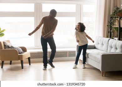 Happy african american dad and kid daughter laughing dancing in living room together, cheerful cute child girl having fun with father moving to music playing at home, black family funny activity