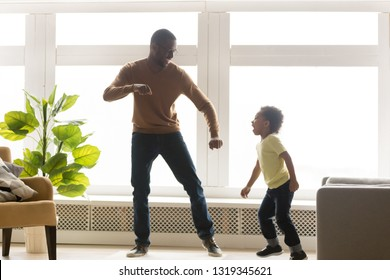 Happy african american dad and little toddler son dancing in living room together, funny kid boy having fun with black father laughing moving to music, daddy baby sitter child play together at home