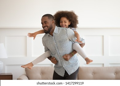 Happy african american dad piggybacking little funny daughter having fun at home, laughing black father carrying cute small kid on back playing together bonding enjoying active leisure in living room