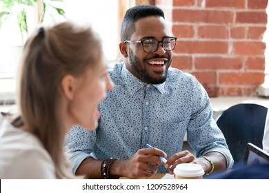 Happy African American employee have fun at casual meeting in office, excited black male worker laugh at colleague joke, talking discussing ideas at briefing, multiracial coworkers smile negotiating
