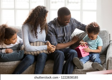 Happy African American family celebrating adorable son birthday, impatient  toddler boy opening pink box with gift, mother and little sister looking at him, loving father pat on head, family event