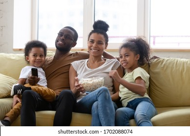 Happy african american family and children watching funny tv show or movie eating popcorn snack. Happy diverse dad holding remote controller, mom hugging cute siblings.