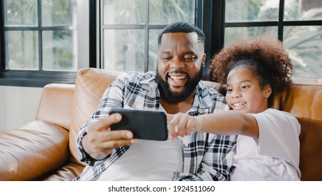 Happy African American family dad and daughter having fun and using mobile phone video call on sofa at house. Self-isolation, stay at home, social distancing, quarantine for coronavirus prevention.