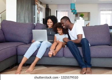 Happy African American family with daughter using laptop at home, shopping online, watching video or movie, smiling mother and father spending weekend together with child, sitting on sofa