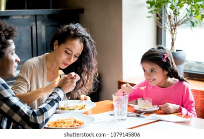Happy african american family eating lunch together at restaurant and having fun