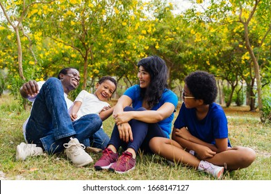 Happy African American family of four hanging out and sitting in the green park. They are laughing and enjoying outdoor activity in summer.