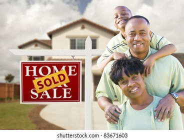 Happy African American Family in Front of New House and Sold Real Estate Sign.
