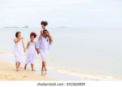 Happy African american family holding hands and walking together on the beach during holiday.