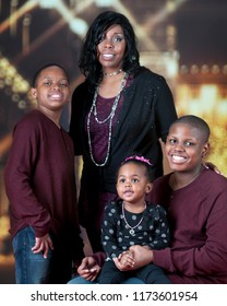 A happy African American family icomposed of a mom, two boys and an adorable preschool girl.  They're standing and sitting with the bright Christmas lights of a Christmas lit mall behind them.
