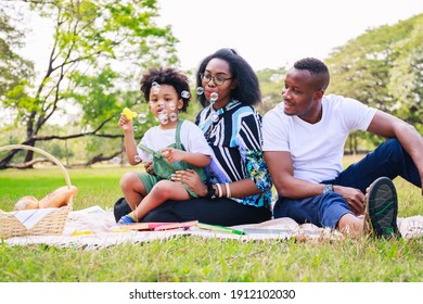 Happy African American family life concept. African American parents (Father, Mother) and little boy enjoying during playing soap bubbles togetherness. family relaxes in green park. Family weekend.