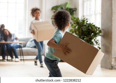 Happy African American family moving in new house, toddler boy carrying cardboard box, playing with preschooler sister, mother and father sitting on couch, looking at children, rear view, close up