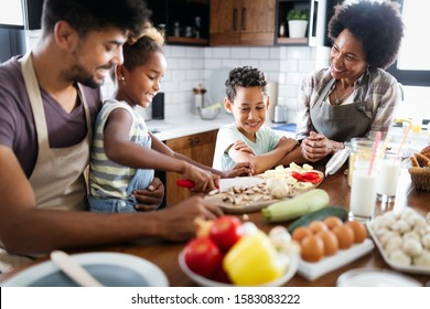 Happy african american family preparing healthy food together in kitchen - Shutterstock ID 1583083222