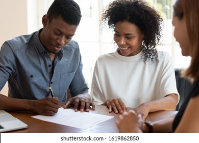 Happy African American family signing contract, legal documents, satisfied clients making deal with realtor or broker, smiling couple wife and husband purchasing new house, taking loan or mortgage
