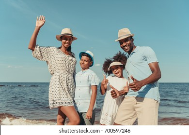 happy african american family smiling at camera and showing thumbs up on beach