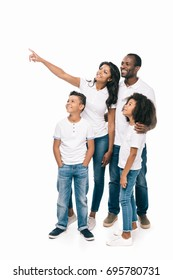 happy african american family standing together and pointing away isolated on white