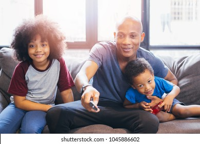 Happy African American family of three watching tv and on sofa at home