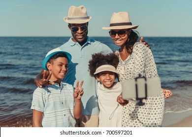 happy african american family with two kids taking selfie with smartphone at seaside