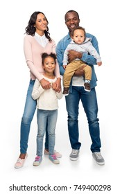 happy african american family with two kids standing together and smiling at camera isolated on white