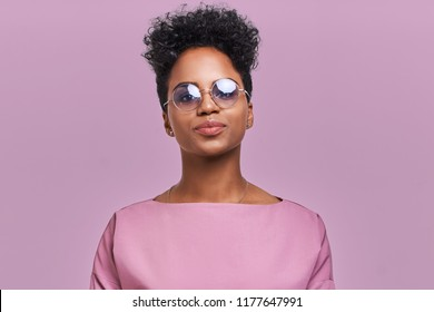 Happy African American fashion woman with sunglasses and positive smile, has crisp dark hair, rejoices having weekend and good rest after hard working exhausting week, isolated on lavender wall