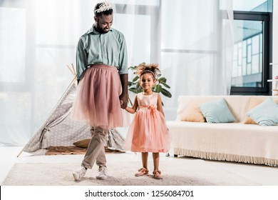 happy african american father and adorable daughter dancing in pink tutu skirts