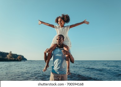 happy african american father carrying adorable little daughter on neck at seaside