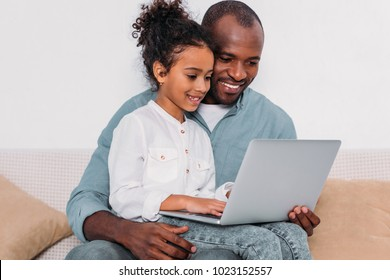 happy african american father and daughter using laptop at home
