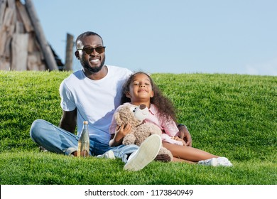 happy african american father and daughter sitting on hill with soda and teddy bear at amusement park