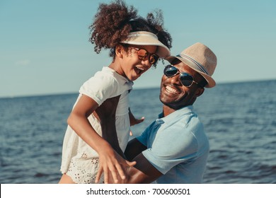 happy african american father and daughter in sunglasses having fun together on beach