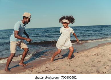 happy african american father and daughter in sunglasses having fun while playing together on sandy beach