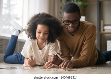 Happy African American father in glasses with preschool daughter assembling jigsaw puzzle, smiling dad and adorable girl child playing on warm floor at home together, family weekend, close up