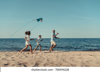 happy african american father and kids playing with kite on beach
