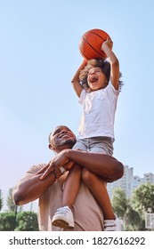 Happy African American father lifting his kid up and helping him score a basketball into a hoop