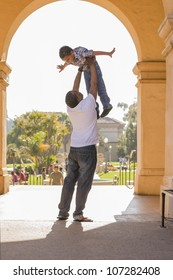 Happy African American Father Lifts Mixed Race Son Over His Head in the Park.