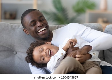 Happy African American father and little son having fun together, laughing dad hugging, tickling cute child, sitting together on couch at home, enjoying weekend, funny activity together close up