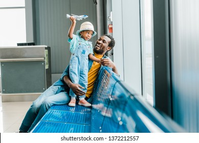 happy african american father looking at son while boy playing with toy plane in airport