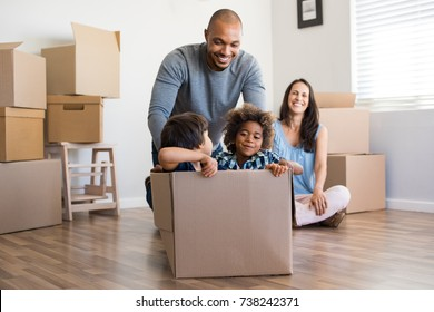 Happy african american father playing with children sitting in carton box at new home. Happy multiethinc family enjoying new home. Young parents and sons having fun during moving house.
