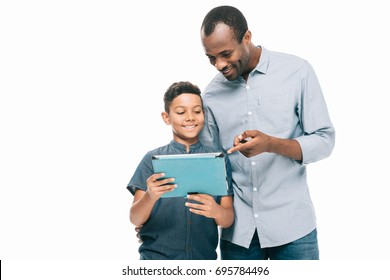 happy african american father and son using digital tablet while standing together isolated on white