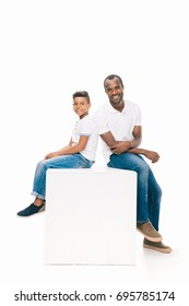 happy african american father and son sitting together and smiling at camera isolated on white