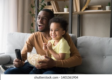 Happy African American father with toddler son, family watching tv, cartoons or football match, eating popcorn snack, sitting on couch together, little boy sitting on smiling dad knees at home