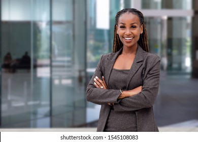 Happy African American female company leader CEO boss executive standing in front of company building