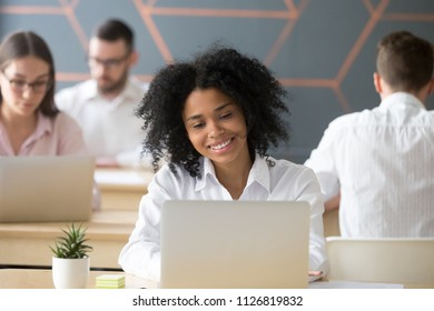 Happy African American female employee working at laptop, satisfied with job she is doing, smiling black woman browsing web, chatting with friends or checking social media in coworking space