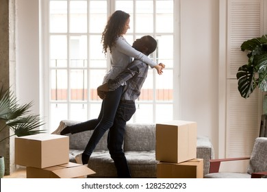 Happy african american first time home buyers couple celebrating relocation or buying house in living room with boxes, excited black man lifting embracing woman enjoying moving day, family goals